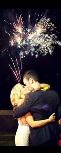 Wedding couple kissing in front of fireworks